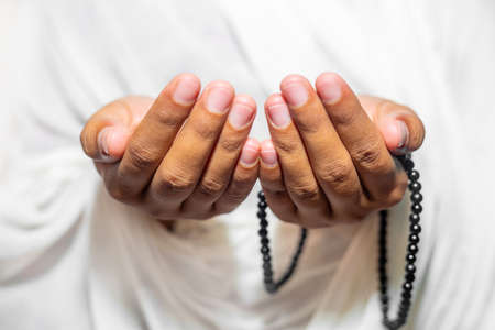 Muslim women raise their hands to pray with a Tasbeeh on white background, indoors. Focus on hands.