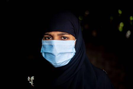 An Asian Muslim girl wearing a surgical mask for coronavirus protection. Hijab woman wearing a mask for safety. Portrait views.