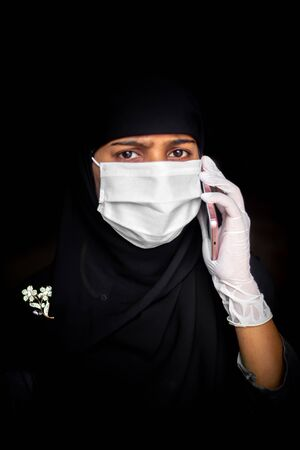 A Muslim girl wearing a safety mask and gloves is talking on her smartphone. Black Hijab woman wearing a blue mask for coronavirus safety.