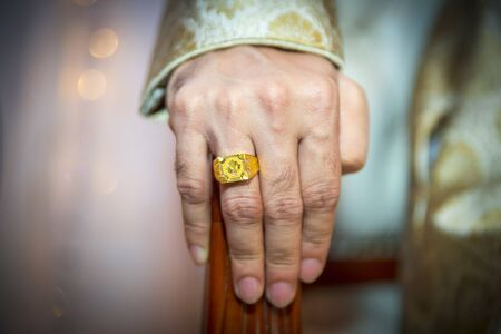 A groom's hand wearing a gold ring. Indian Wedding. Standard-Bild