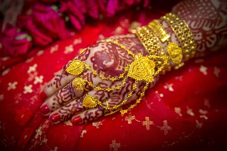 A bride's hand full of gold ornaments. Indian Wedding.