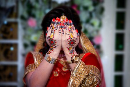 A bride covers her face with both hands. Indian Wedding.