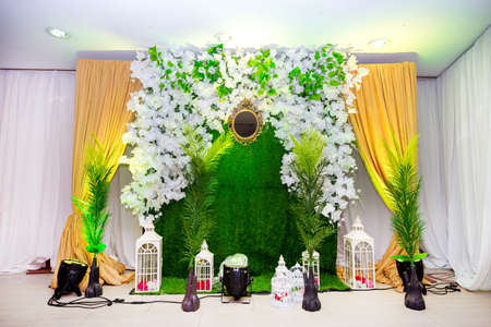 Green artificial grass based wedding stage with artificial colorful paper flower decoration.