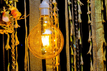 Colorful artificial flowers with Decorative antique Edison style filament light bulbs hanging on wedding stage decoration.