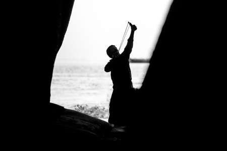 A men takes aim and hunting bird using on a Slingshot. Image of against sunlight. Silhouette image.