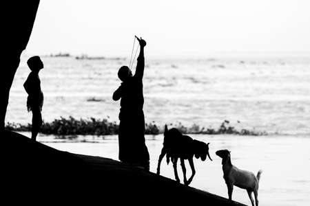A man aiming a traditional bird hunting machine called Slingshot. Image of against sunlight. Silhouette image.