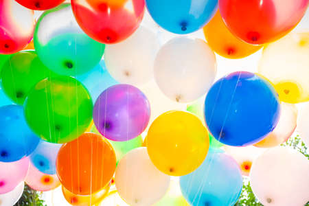 Sunlight against colorful gas-filled balloons attached to the yarn. Colorful balloons background.