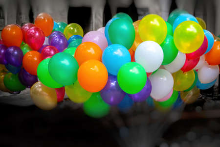 A bunch of colorful gas-filled balloons on dark background.