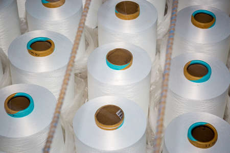 Top view of A lot of white yarn spools in a textile factory. White yarn spools in a clothing factory. Stock Photo