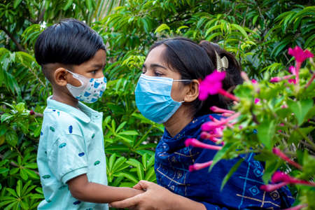 Asian mothers and children wearing safety masks are spending a good time in the green garden. Covid-19 pandemic, Lockdown, and home quarantine time safety concept. Educational and safety concept.