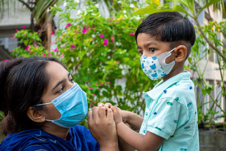 Asian mother teaches her child about the need to wear a safety mask in a green garden. Covid-19 epidemic, Lockdown and home quarantine time safety concept. Educational and safety concept.
