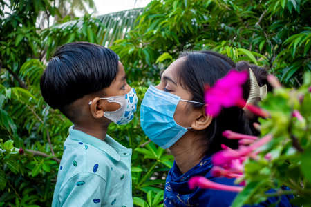 Asian mother and child are kissing and loving each other while wearing safety masks. Hygiene and safety concept. Mom and the kid have happy moments in the green garden.