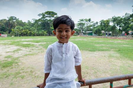 A white Punjabi-wearing smiling asian kid is sitting on a steel pipe. A Muslim boy is wearing a white Punjabi modern outfit.