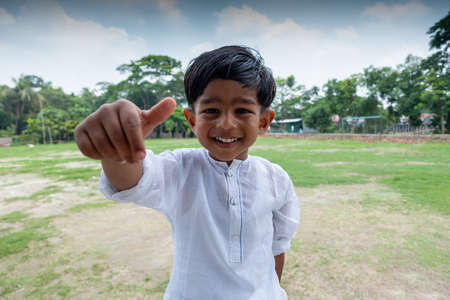 A white Punjabi-wearing kid doing fun with using his hands and looking at the camera. A Muslim boy is wearing a white Punjabi modern outfit at the outdoor field.