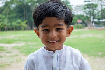 A white Punjabi-wearing two years boy is smiling and looking at the camera. 2-year kid face close-up views. Standard-Bild