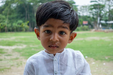 A white Punjabi-wearing two years boy is looking at the camera with a curious face. 2-year kid face close-up views. Standard-Bild