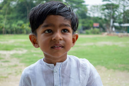 A white Punjabi-wearing two years boy is looking at away. 2-year kid face close-up views. Standard-Bild