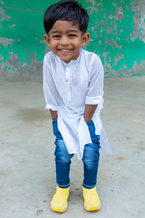 A smiling kid is posing for a photo wearing white Punjabi and blue jeans with a yellow shoe as a modern dress. A modern outfit is white Punjabi and blue jeans. A two years boy's modern outfit and style.