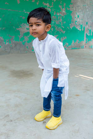 A smiling kid is posing for a photo wearing white Punjabi and blue jeans with a yellow shoe as a modern dress. A two years boy is looking at the away with a curious face.
