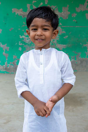 A white Punjabi-wearing two years kid is smiling and looking at the camera. 2-year kid face close-up views. A funny Asian boy is facing a camera.