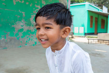 A white Punjabi-wearing two years kid is smiling and looking at away doing for fun. 2-year kid face close-up views.
