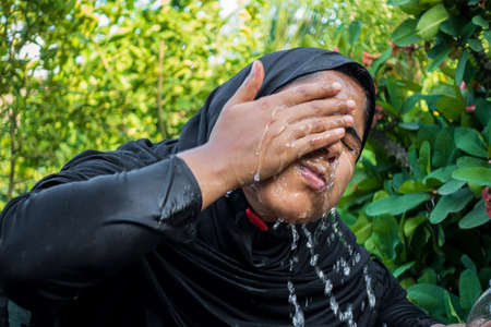 A woman splashes cold water on her face on a hot day. A Muslim woman dressed in black is performing ablution with water. The concept of cleaning the face with water.