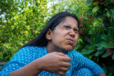 A woman splashes cold water on her face on a hot day. Closeup view of a young girl cleaning her face with water. Happy beautiful girl washes her face with pure water.