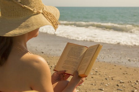 Beautiful woman reading a book on beach Antalya