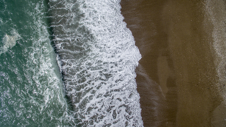 Aerial view waves break on white sand beach. Sea waves on the beautiful beach aerial view drone