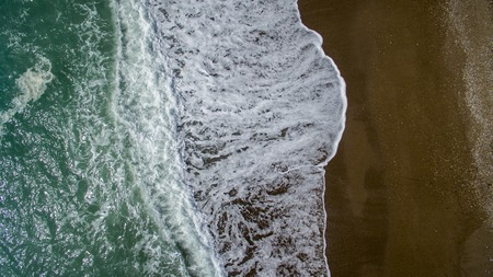 Aerial view waves break on white sand beach. Sea waves on the beautiful beach aerial view drone