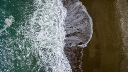 白い砂浜で空中写真の波が壊れます。美しいビーチ空中ビュードローンの海の波