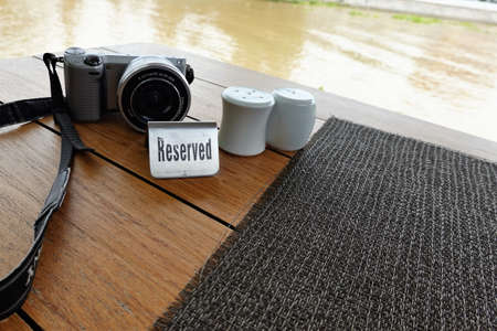 The table reservation sign is set on a placemat made of black weave material, complete with a bottle of chili, salt and a camera