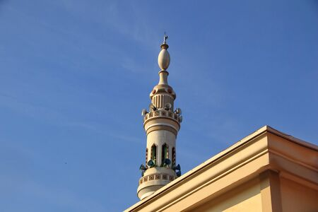 a mosque tower that resembles a nabawi mosque tower in Madina Mecca, but it is not perfectly made of shapes or altitude, with a blue sky