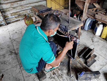 radiator repairman when cleaning and repairing broken radiators in old cars. In a car workshop, Pekalongan - Jawa Tengah - Indonesia, June 1, 2019 Editorial