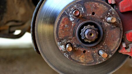 Disc brake of the vehicle for repair, in process of new tire replacement. Car brake repairing in garage.Close up. with selective focus