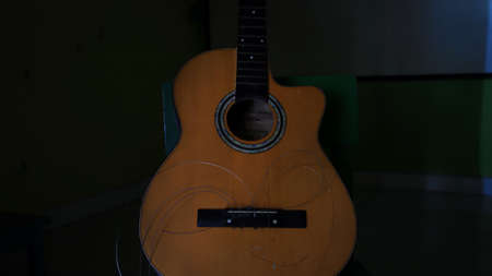 Not focus and noise image, damaged acoustic guitar, with the strings not attached, can't be plucked