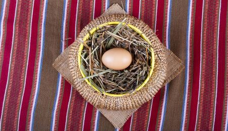 easter basket with egg on a striped tablecloth