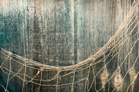 Fishing net on vintage wood, maritime nautical background texture.