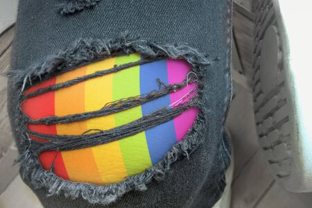 Young fashion man's legs in jeans. Hole and Threads on Denim Jeans surface with LGBT pattern.