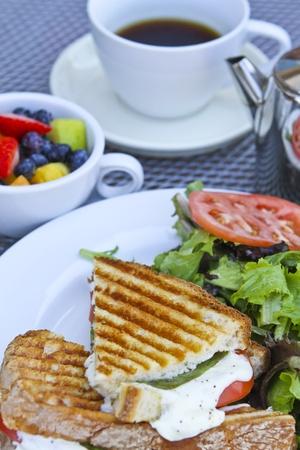 sandwich de pollo: Panini desayuno con frutas complementando y t� en las placas blancas. Foto de archivo