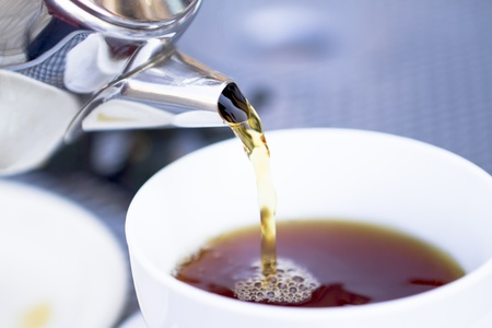 Pouring hot black tea from restaurant style cattle. Selective focused on kettle and poured tea. Stock Photo