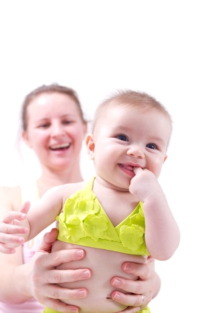 Baby in yellow bikini held by mother, she smiles while sucking her hands.