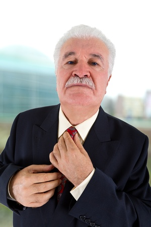 Experienced Businessman Adjusting His Tie photo