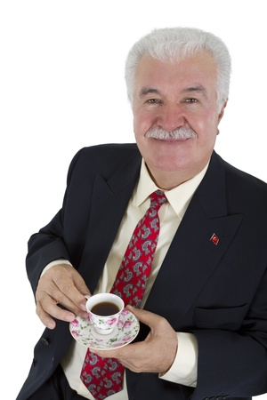 Turkish business man drinking his coffee, wearing red tie and suit. Isolated on white. Stock Photo