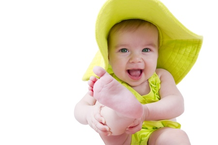 Green eye baby holding her leg. She is wearing a bright green hat. Here is my leg take this. Stock Photo