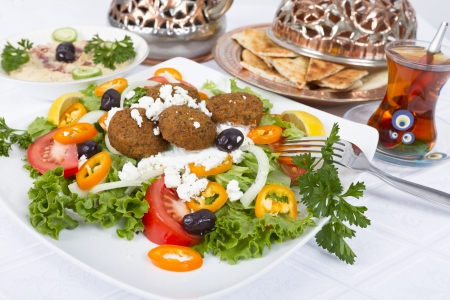 Falafel Salad with Pita Bread and Hummus plate, complimented with tea on a white table cloth.