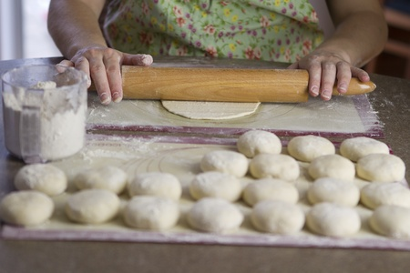 A lady flatten the dough to make flat bread pizzas using classic wooden roller. Stock Photo