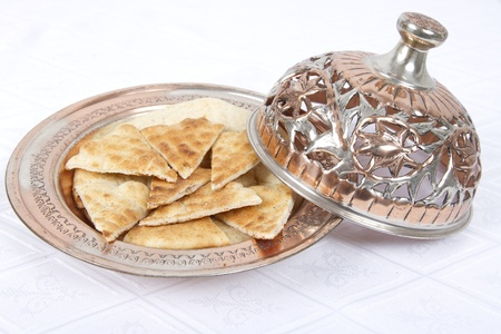 Fresh Pita Breads are served in Ottoman style copper bowl. photo
