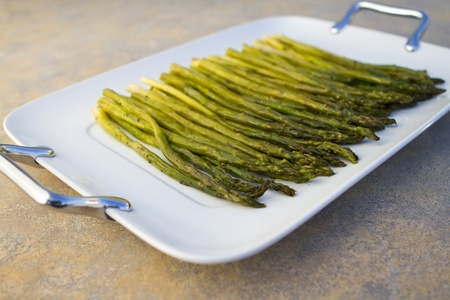 Cooked asparagus on a white square plate on concrete countertop.
