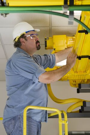 A telecommunication switch worker inspecting Fiberoptic cables in the fiberduct on a ladder platform. He is wearing hardhat and safety glasses. Surrounded by grounding telecom equipment cables. Stock Photo